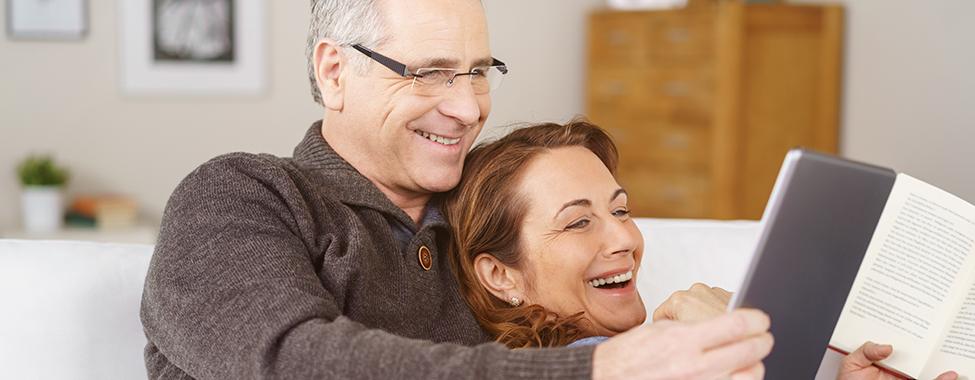lachender mann zeigt seiner frau etwas am tablet