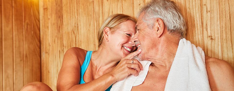 Verliebtes Senioren Paar sitzt zusammen in der Sauna im Wellness Hotel