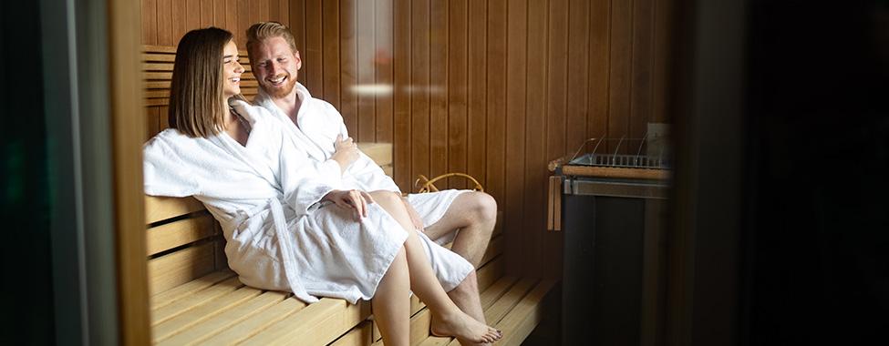 Happy-Couple-Sitting-on-Sauna-Bench