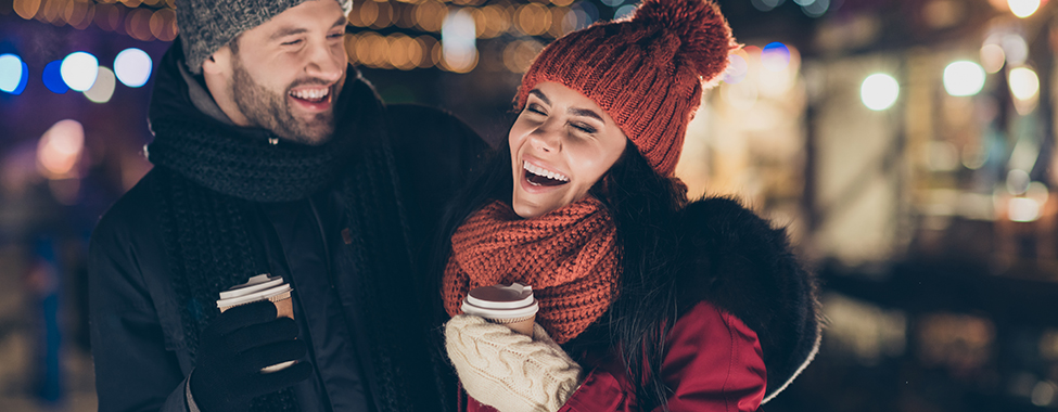 Photo of two people with hot beverage spending last evening in year, outdoors having best time wearing warm jackets knitted hats and scarfs