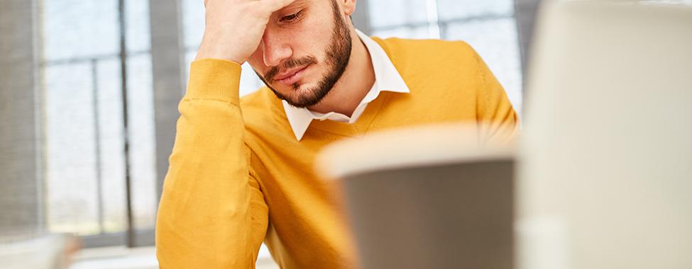 Junger Mann als Geschäftsmann im Büro denkt über ein schwieriges Problem nach