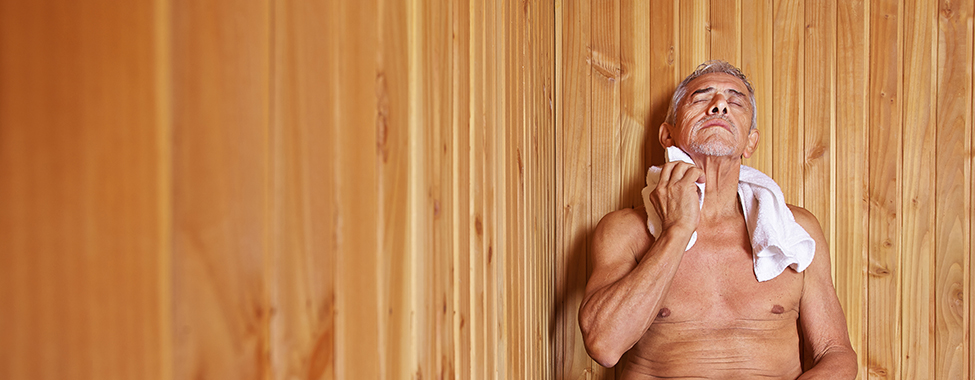 Old man with towel relaxing in sauna of a hotel
