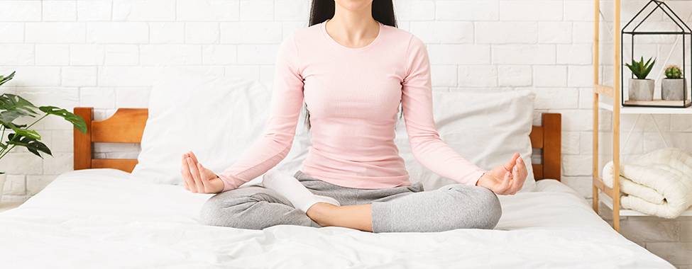 Young woman start her day with meditation, sitting on bed in yoga position, panorama