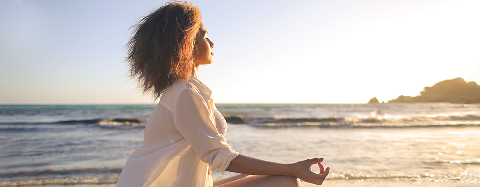Woman-Meditating-on-Beach-for-Vacation-Mental-Health