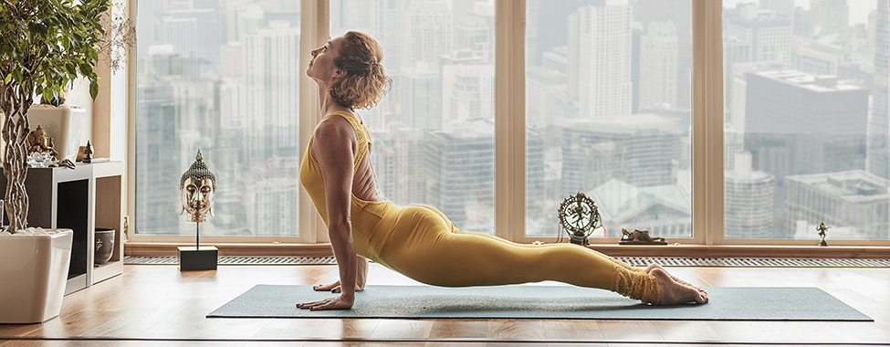Confident young girl is stretching her body while leaning on hands. She is exercising on mat near window