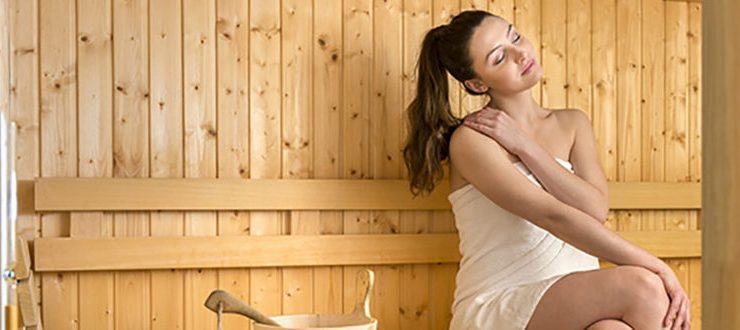 Woman-Relaxing-in-Sauna-and-Massaging-Neck-lg3-750x330