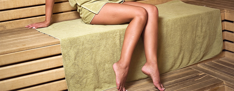 Woman-Sitting-on-Towels-in-Infrared-Sauna