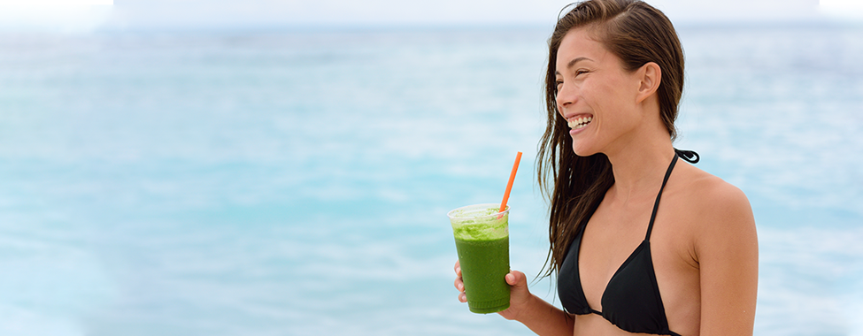 Woman-Staying-Fit-on-Vacation-with-Green-Smoothie-on-Beach