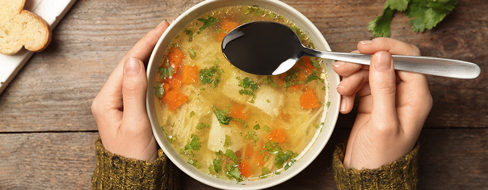 Person Eating Healthy Chicken Soup for Cold Remedy